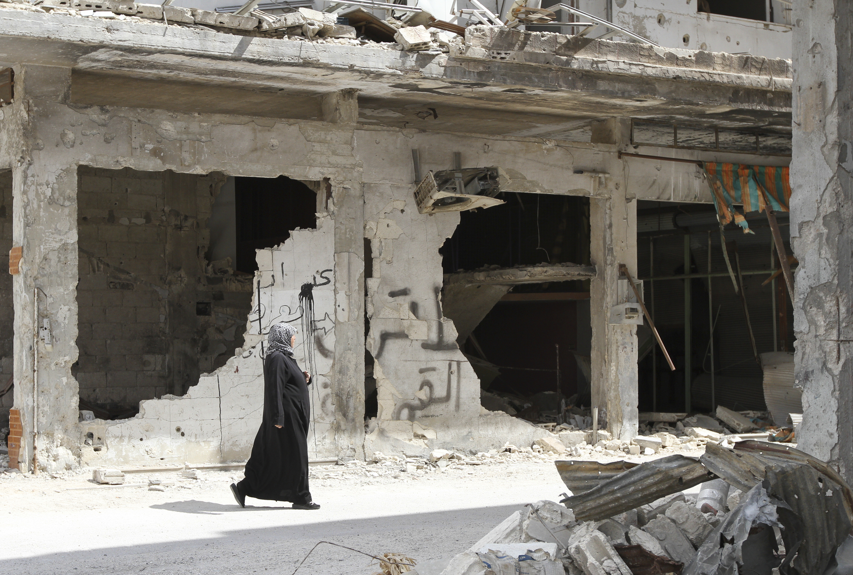 Homs, Syria - September 22, 2013: A woman walks near a house in the city of Homs destroyed in the fighting between the rebels of the Syrian National Army