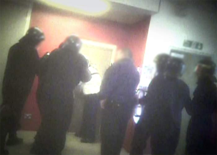 BBC: Officers in riot gear prepare to enter a room